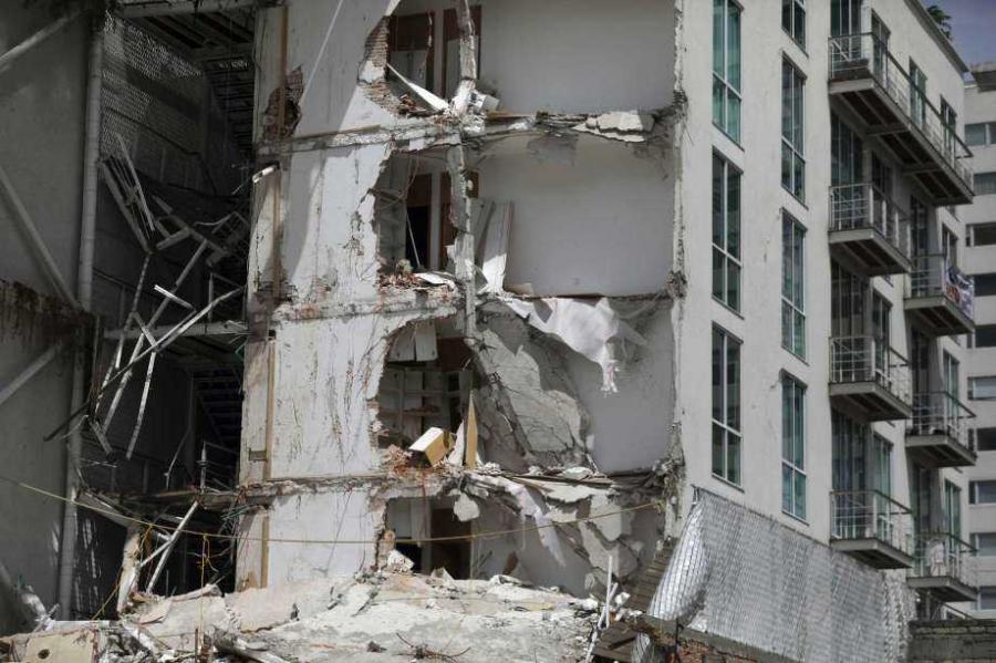 This Sept. 24, 2017 photo shows an apartment building that was partially destroyed during the 7.1 magnitude earthquake, on Emiliano Zapata Avenue in Mexico City. The eco-friendly apartment building with its wood-paneled balconies and a solar-paneled roof collapsed when a corner column failed, and the flat-slab structure pancaked, said Eduardo Miranda, a professor of civil and environmental engineering at Stanford and global expert on earthquake-resistant design.  (Photo Credit: AP)