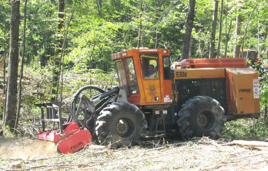 A Power Equipment Company representative demonstrates how effectively the Barko 930B mulcher with a Fecon forestry mulching head rips up felled trees and limbs.