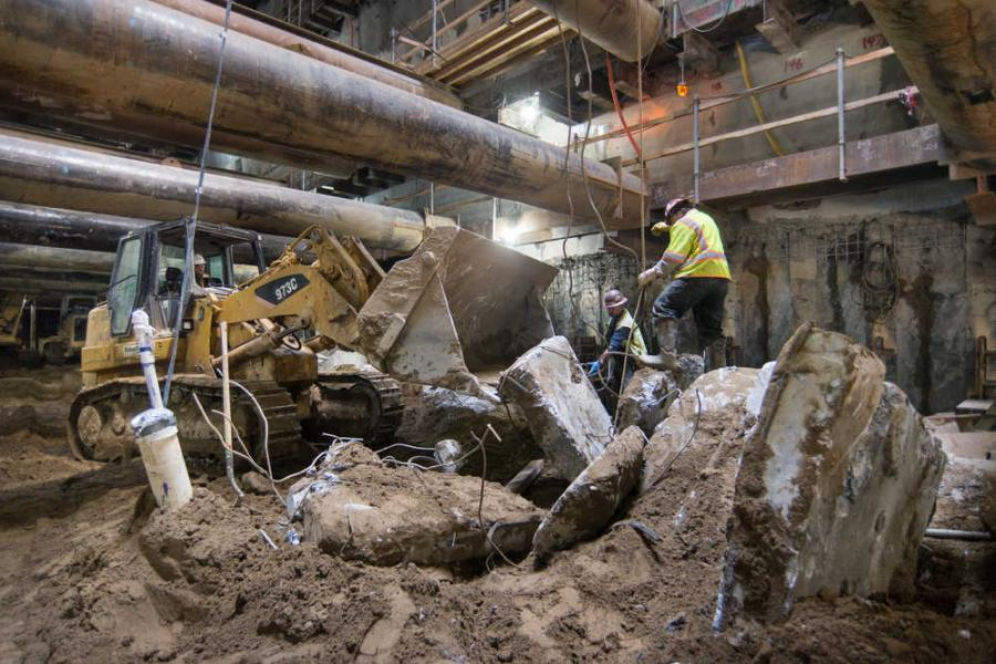 A crew uses a bulldozer to collect demolished pieces of tunnel ring segments removed from inside the station box.