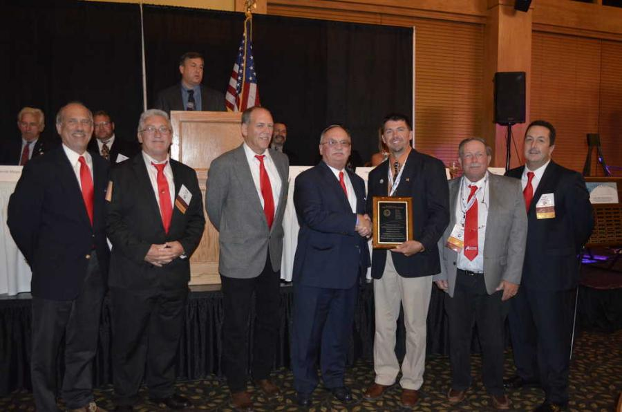 Russ Scherrer (4th from L), president of Auctions International, accepting the VISION award from Mike Boesel (5th from L),  outgoing president. (L-R) are Sales Representatives Marc Smith, Bob Anderson, Tom Eagan, Scherrer, Boesel, Jeff Laxton and Jim Giovaniello.