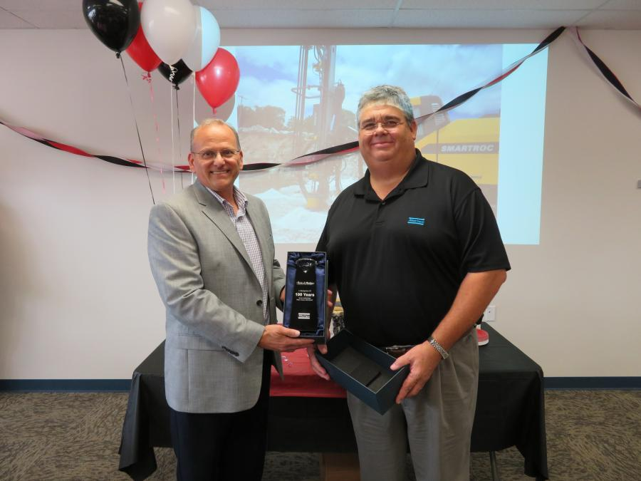 Jerry Enyeart (L), Atlas Copco district manager, presents Bill Schoenfelder, president of The Victor L. Phillips Company, with an award recognizing 100 years as an Atlas Copco dealer.
