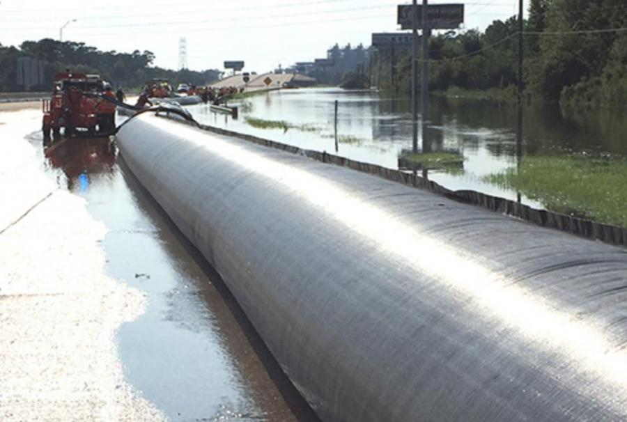 TxDOT crew members begin AquaDam deployment on a flooded stretch of I-10. (TxDOT photo)