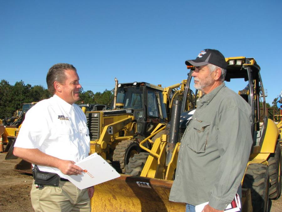 Jason Green (L), Jeff Martin Auctioneers, provides more information about the equipment at the auction to Sam Pittman, independent contractor based out of Sumrall, Miss.