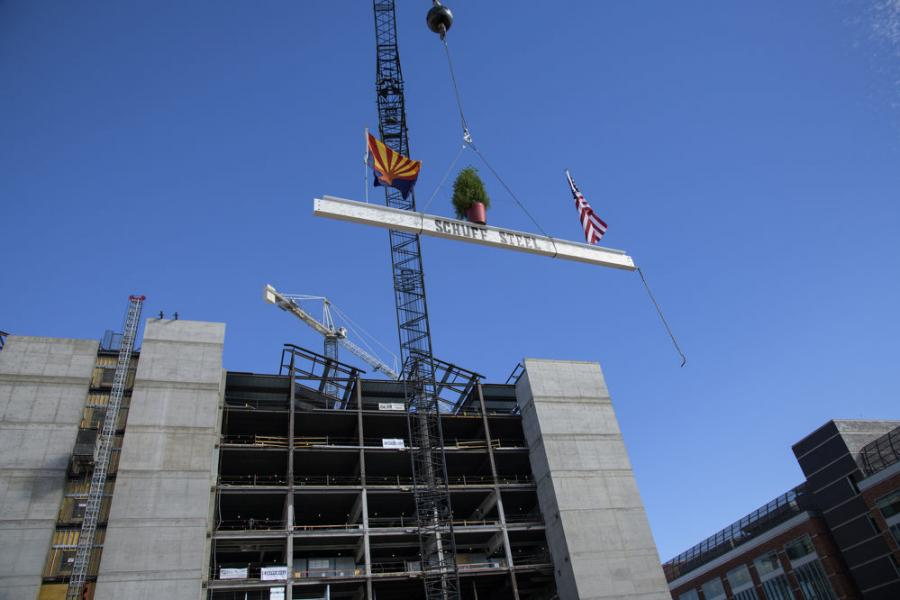 """Covered with signatures and bedecked with U.S. and Arizona flags and a small ceremonial tree, the beam rose above the crowd that had gathered for the Nov. 17 """"topping-off"""" ceremony. (University of Arizona photo)"""