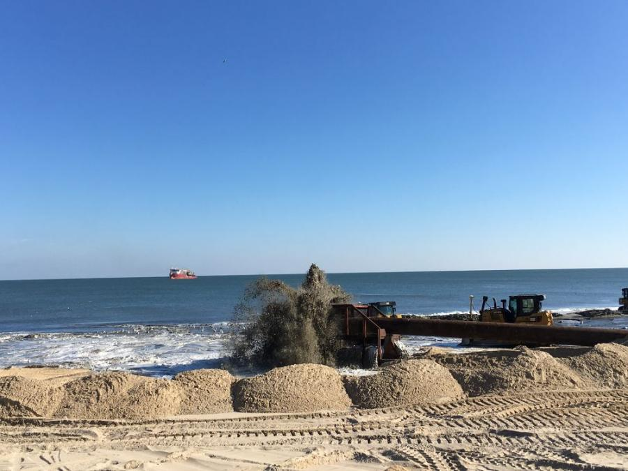 A sand and water slurry mixture is pumped onto the beach at Ocean City, Md., from an offshore dredge visible in the distance during beach renourishment work Nov. 20, 2017. 
