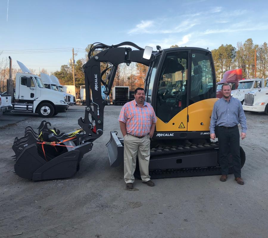Scottie Holcomb (L), product support manager, and Brian Meissen, sales manager, both of Reynolds-Warren Equipment Company stand with one of the first Mecalac machines delivered to the company's Forest Park, Ga., headquarters facility.