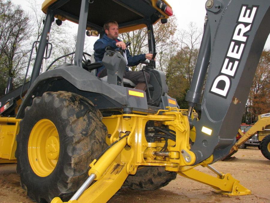 Jason Lambert, Lambert Equipment, Samson, Ala., test operates a John Deere 310SJ backhoe loader.