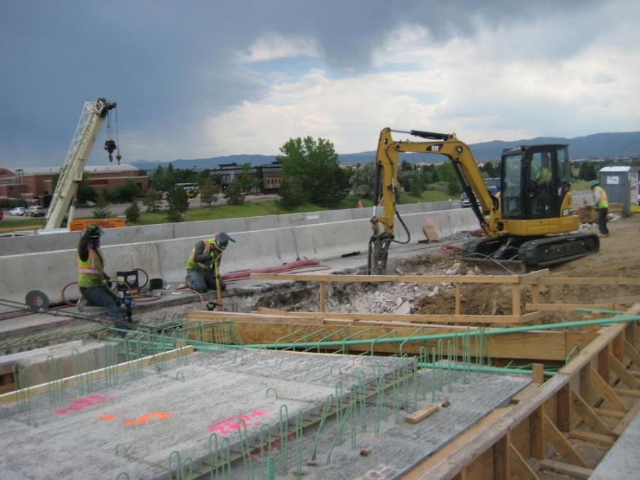 A Caterpillar 305 excavator chips concrete to widen a bridge on the C-470 express lane project in Denver.