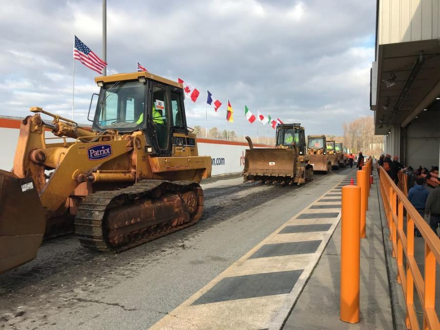 Caterpillar crawler loaders rumble over the auction ramp.
