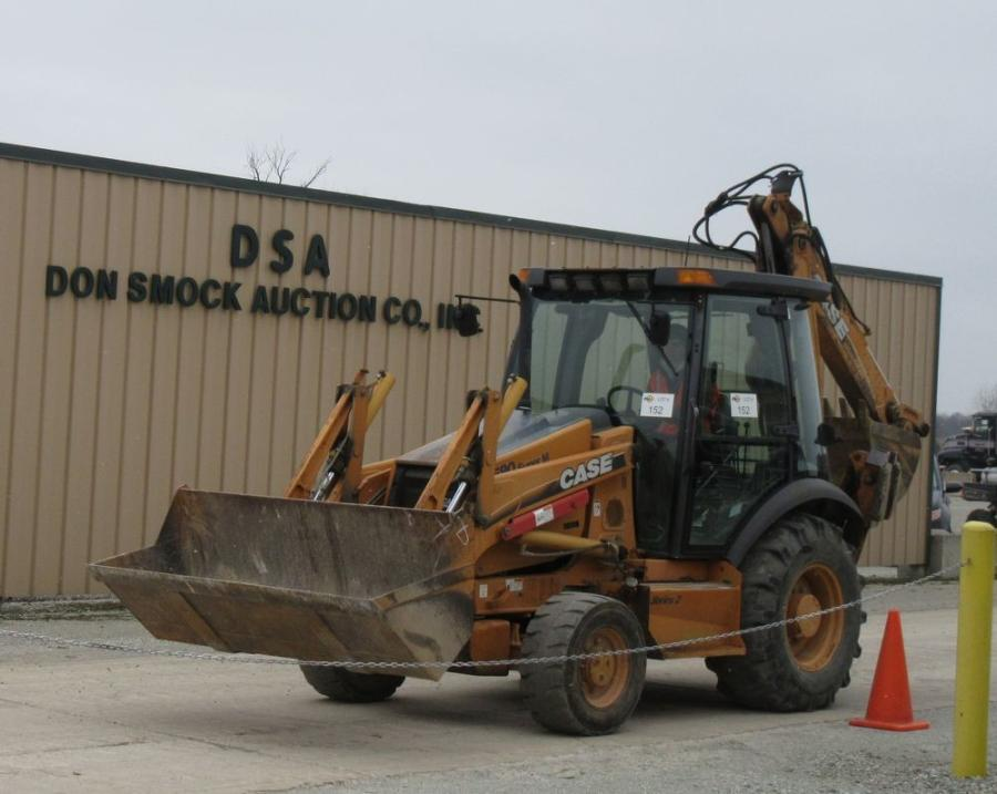 A Case backhoe rolls off the ramp.
