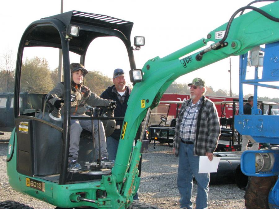 (L-R): Eight-year-old Daniel shows his dad, Donny, and grandfather, Rodney Noland, all of Noland Services Inc., Carrollton, Ala., just what he can do with a JCB 8018 mini-excavator.