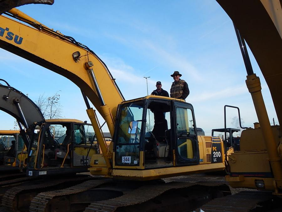 "Pat Pemberton (L), owner of Cascade Mechanical Systems, Estacada, Ore., and Steve Mueller, owner of Crest Power Equipment, Estacada, Ore., are considering this Komatsu 200LC excavator. ""We are looking for excavators, dump trucks, golf carts and any other deals we can find,"" said Pemberton."