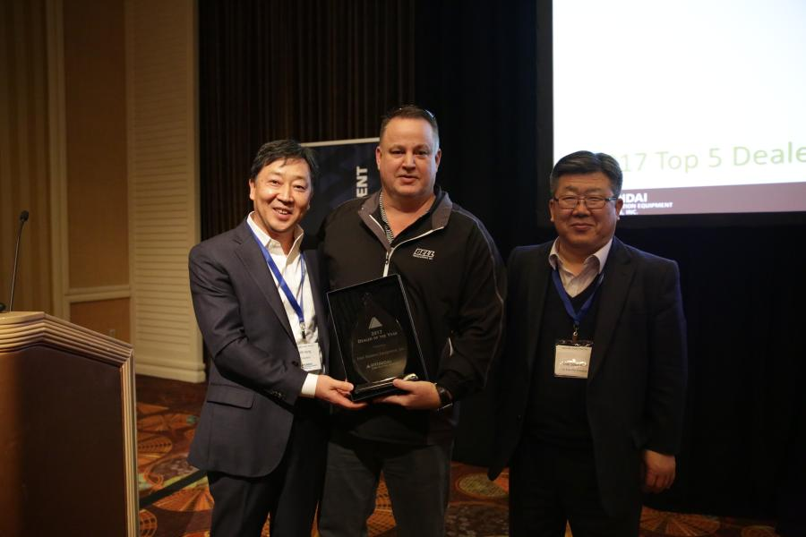 M.S. Kang (L), president of Hyundai Construction Equipment Americas, and Dai Soon Kim (R), senior executive vice president, Hyundai Construction Equipment — Korea, present the Hyundai 2017 Dealer of the Year Award to Mitch Nevins, CEO of Four Seasons Equipment.