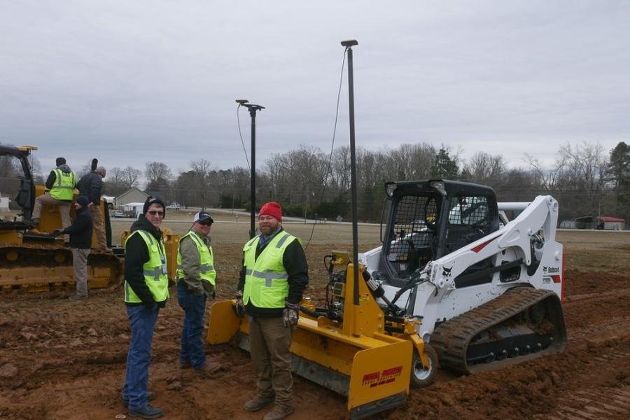 Two attendees speak with Benchmark Sales Rep Andy Pugh (right) about the Hitch Doc Dual Dozer with Topcon Components attached to a Bobcat Skid Loader.