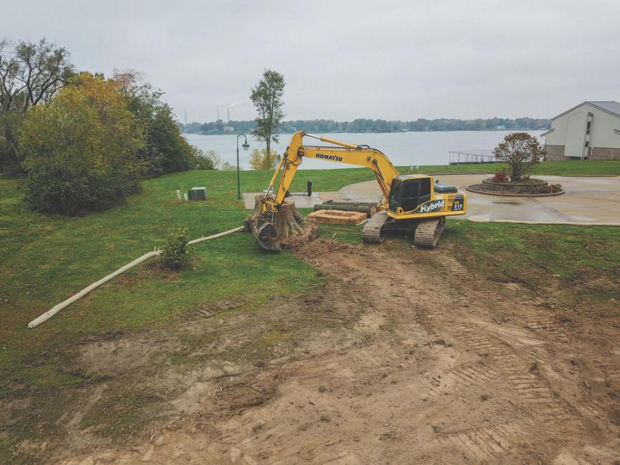 Operator Michael Chandler uses one of Professional Excavating's Komatsu Hybrid HB215LC-1 excavators to move a nearly 4,000-pound stump as he preps a site before digging a basement.