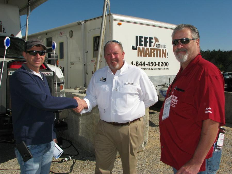 Jeff Martin (C) gives a warm welcome to his friends and customers, including John Tindal (L), Tindal Truck Sales, Mayfield, Ky., and Charles Whitney, a land development contractor based locally in Brooklyn, Miss.