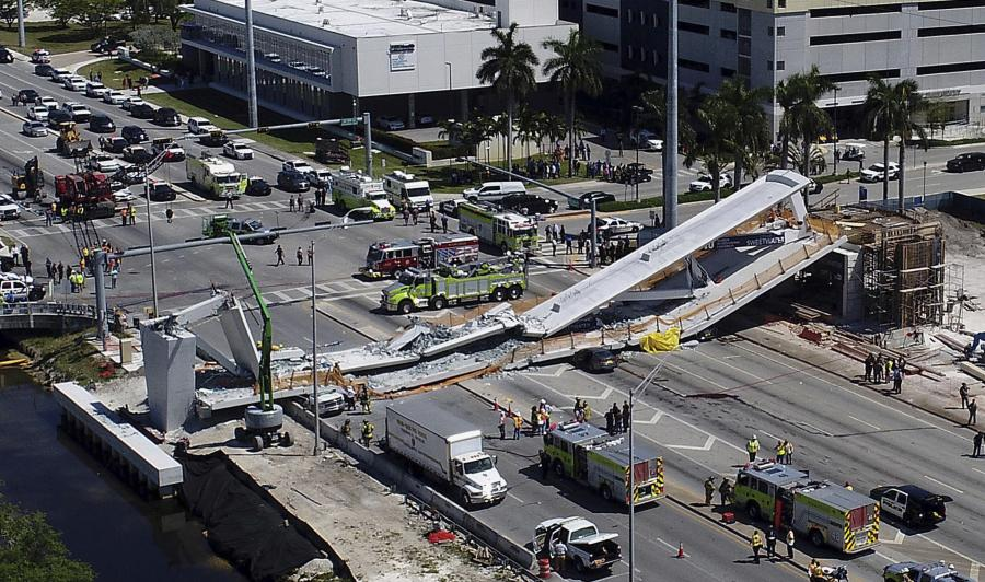 Emergency personnel respond after a brand-new pedestrian bridge collapsed onto a highway at Florida International University in Miami on March 15. The pedestrian bridge collapsed onto the highway crushing multiple vehicles and killing several people. (Pedro Portal/Miami Herald via AP photo)