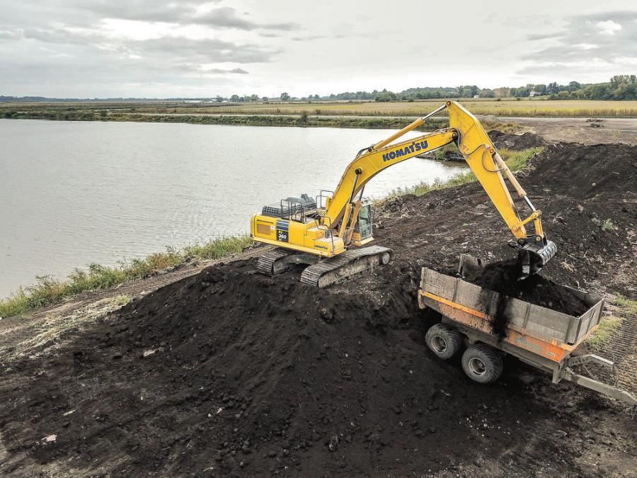 "A Markman Peat operator uses a Komatsu PC360LC excavator to load peat moss that was harvested from the adjacent bog. ""The PC360 has excellent power, which is great because we are usually pulling loads of wet dirt from the ground at full extension,"" said President Jeff Widdop."