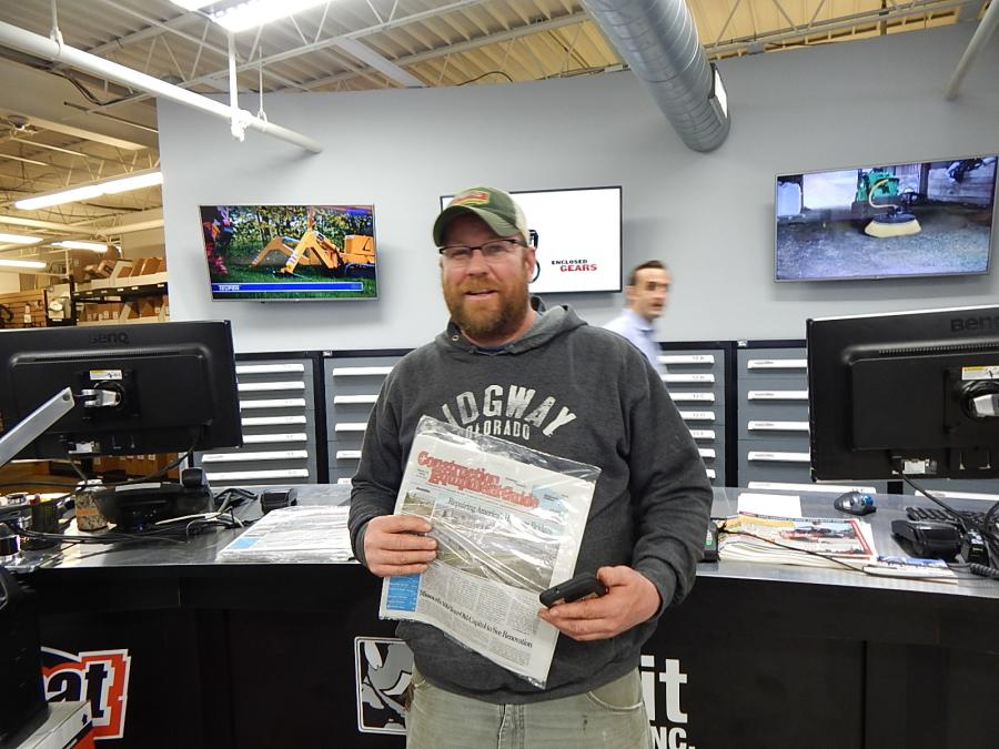 Mathew Molinaro, owner of Molinaro Tree, Minneapolis, Minn., picks up his copy of Construction Equipment Guide.