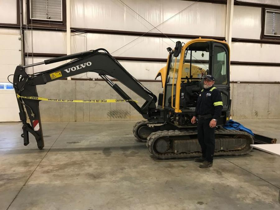Tom Mader, lead technician of Highway Equipment & Supply Co., Harrisburg, with the Volvo excavator that Highway Equipment & Supply Co. provided for the electrical diagnosis station.