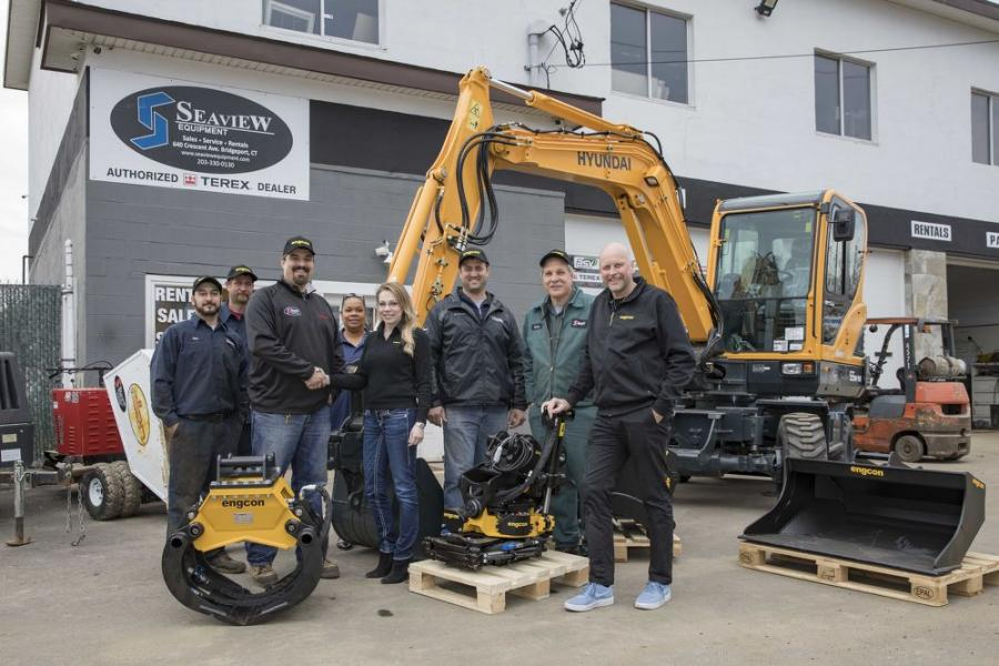 Paulo Lage (3rd from L), general manager of Seaview Equipment LLC, and Joanna Tromczyk (5th from L), head of sales of Engcon North America, shake hands while Krister Blomgren (far R), CEO of Engcon and other company representatives look on.