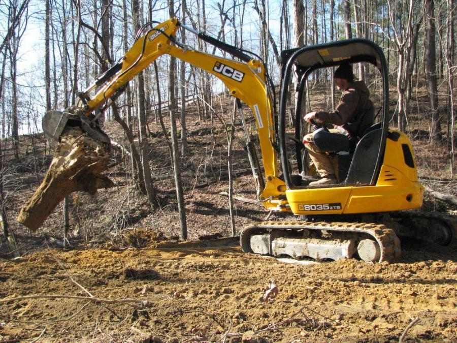 A McAlister Grading machine operator clears debris on a job site using a JCB 8035 ZTS.