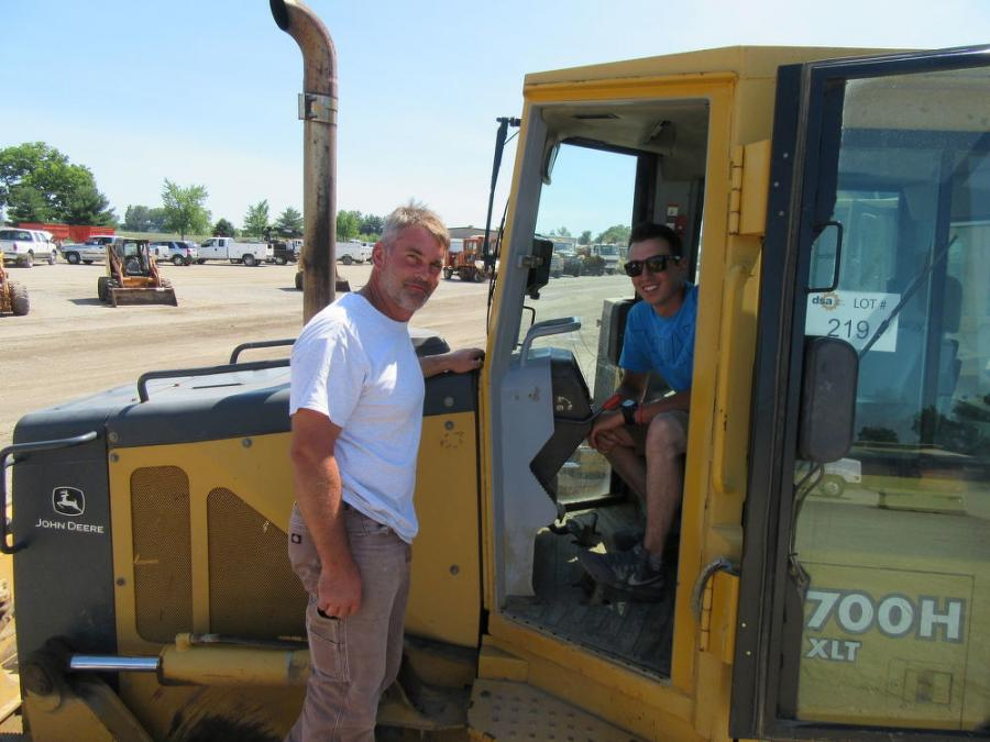 Jared Shront (L) and Greg Nottingham of Nottingham Excavating consider a bid on this John Deere 700H dozer at the auction.