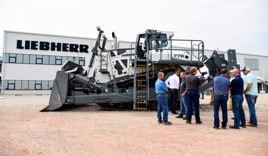 Crowd of customers discuss the PR 776 dozer with product specialists.