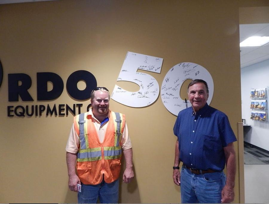 Jerrod Rudnitski (L), Ames Construction equipment manager, Burnsville, Minn., and Ames President Raymond Ames pose with the autographed RDO sign.