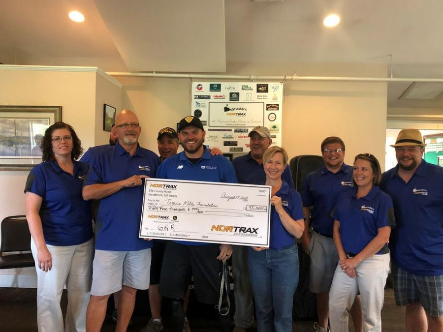 The Nortrax team presents the proceed check. (L-R front row) are Kim Voisine, John Paradis, Travis Mills, Kelly Labbe, Melissa Cry and Mike Bean. (L-R back row) are Glenn Connell, Mike Sullivan, Armand Richard and Tim Pomerleau.