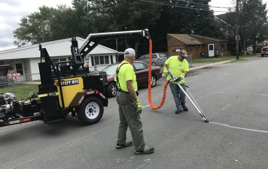 Mayor Tony Fuga (R), Jermyn Borough, and a road department member implement the borough's new road preservation plan by sealing the first of many asphalt cracks on the borough's roads. Using the Stepp Manufacturing crack sealer purchased from Stephenson Equipment's Wilkes-Barre branch, they will be extending the life of the roads by many years.