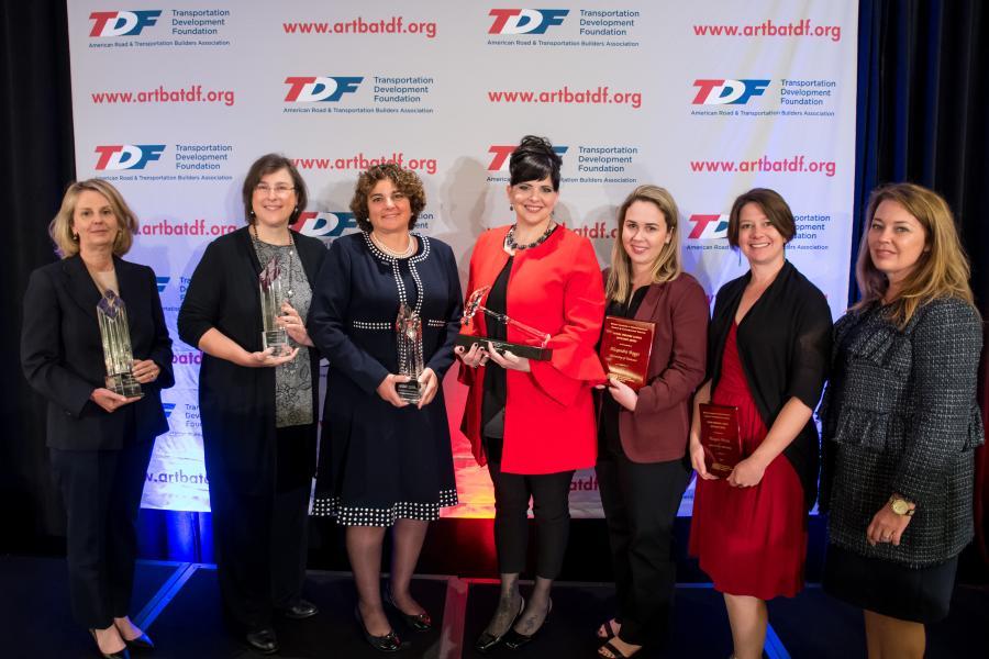 (L - R) are 2017 winner Diane Woodend-Jones, Lea and Elliot; Melissa Tooley, TTI; Diana Mendes, HNTB Corp.; Judy Hricak, Gannett Fleming; Alexandra Boggs, University of Tenn.; Meagan Brown, Grand Canyon University; and Lisa Robert, RS&H.