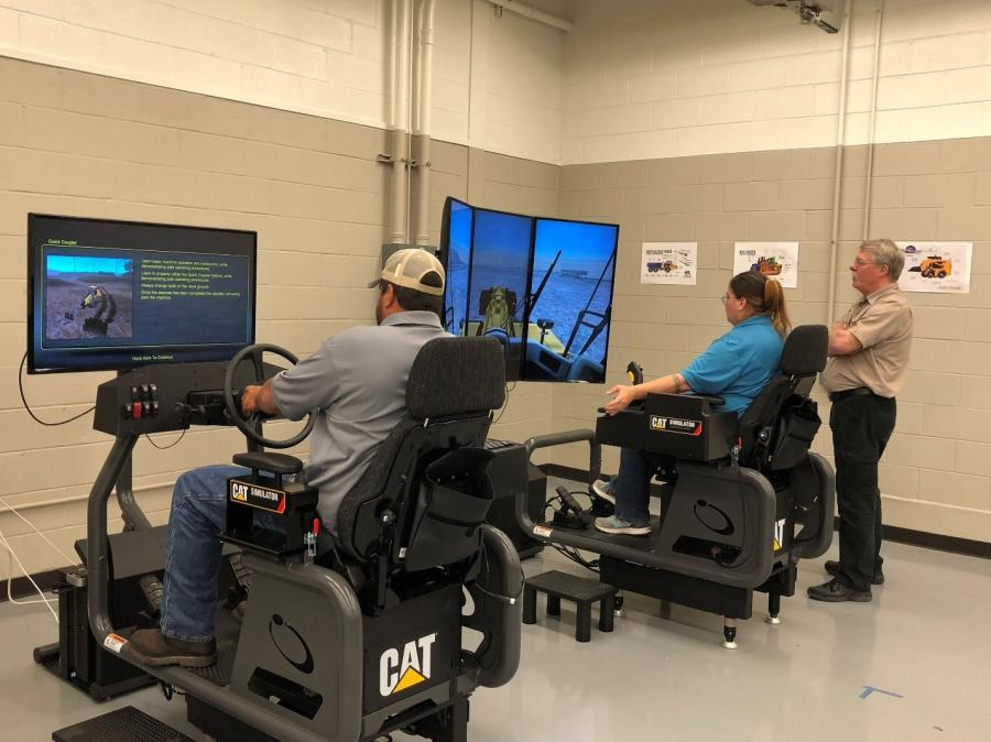 HEO instructor McDonough operates the Caterpillar small wheel loader simulation with motion platform next to the large wheel loader.