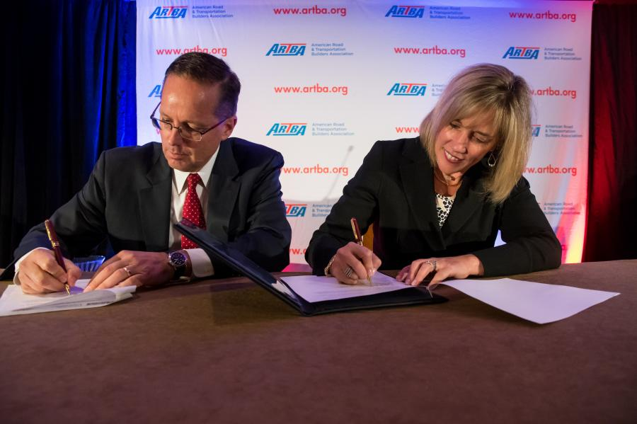2017-18 ARTBA Chairman Matt Cummings of AECOM and WTS International Chairwoman Maggie Walsh of HDR sign the MOU.