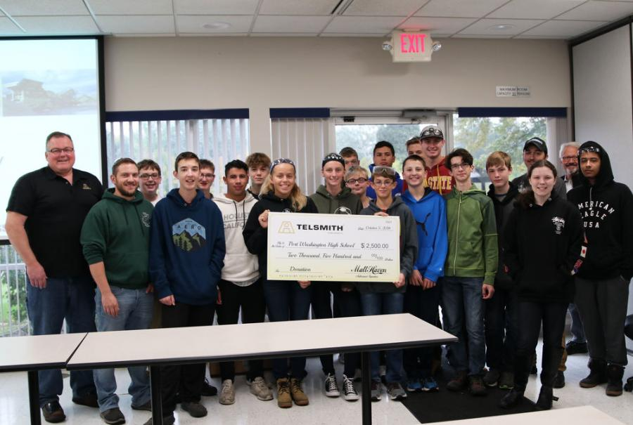 Port Washington High School students pose with a large check from Telsmith Inc.