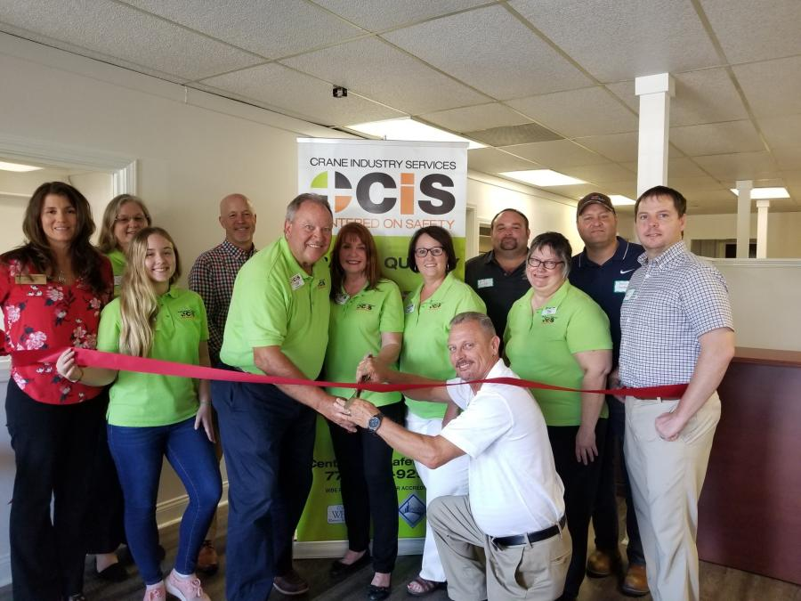 Barry Garrett, Maxim Crane Works, cuts ribbon, along with Cliff and Debbie Dickinson at the CIS Open House.
