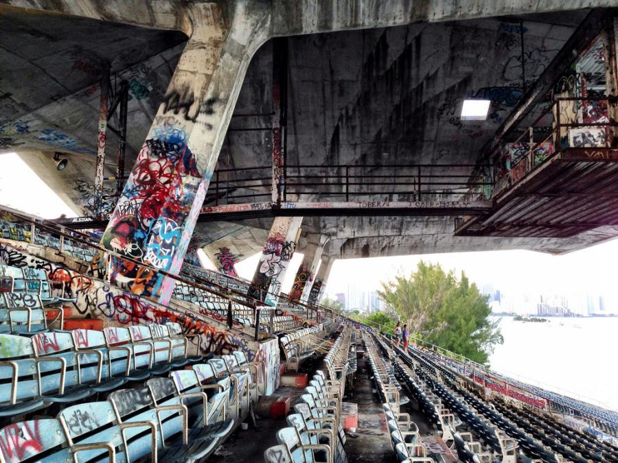 The stadium's rooms and concourses have been stripped bare, corroded by the elements. Rusted light fixtures from the vaulted cantilever roof have crashed to the ground and wedged themselves between aisles of janky seats. Layers upon layers of graffiti have spread like invasive vines across every wall. (Photo Credit: Flickr)