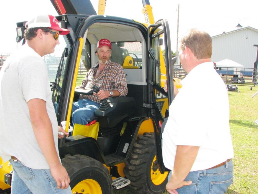 Neil Rountree (R) of MacKinnon JCB, Tifton, Ga., talks with the guys from Dewayne Oaks Poultry Waste Management, based in Eva, Ala., about the advantages of utilizing a JCB Teleskid in their operations.