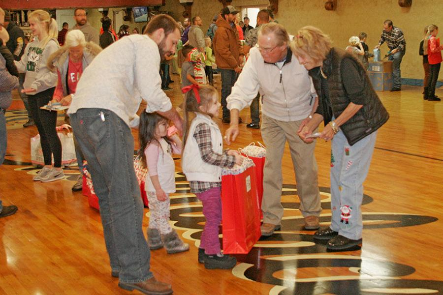 Gary and Sharon Godbersen present gifts to the five-year-old girls. Gary is the GOMACO president and CEO, and Sharon is the vice president of accounting.