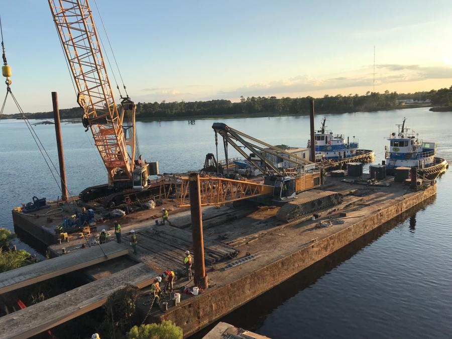 The first project crane is delivered to the construction site by barge.