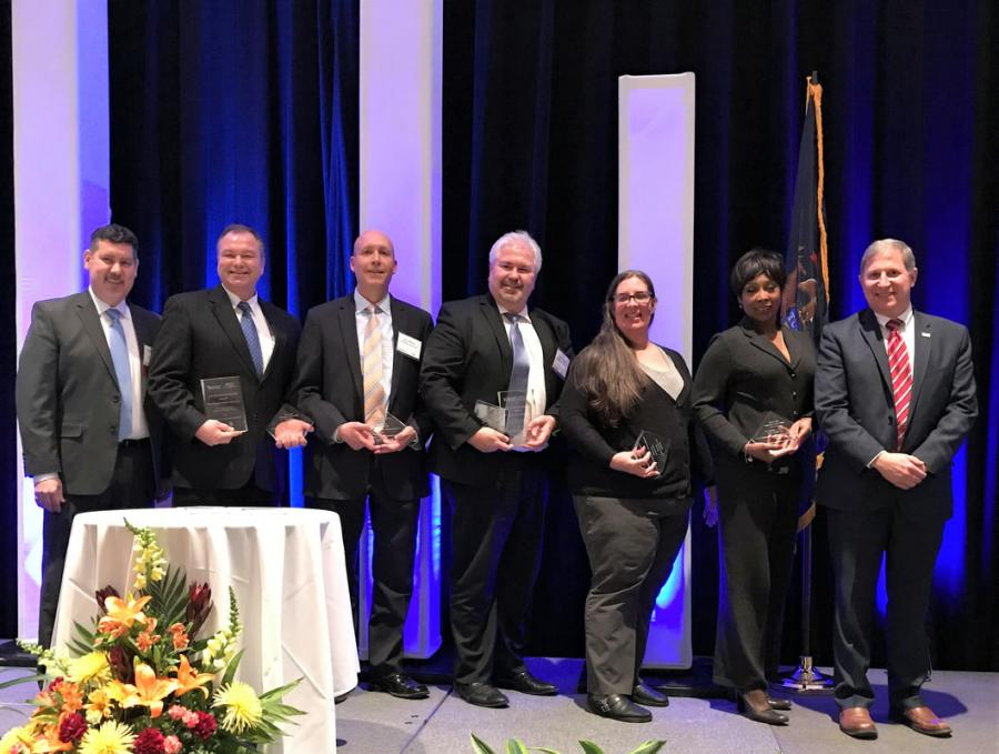 (L-R): Tony Kratofil, PE; Terry Stepanski, PE; Eric Polvi, PE; Matt Simon, PE; Carrie Warren, PE; Dr. Audrey Andrews; and Ronald Brenke, PE, share the 2019 MDOT ACEC Partnering Charter Award.