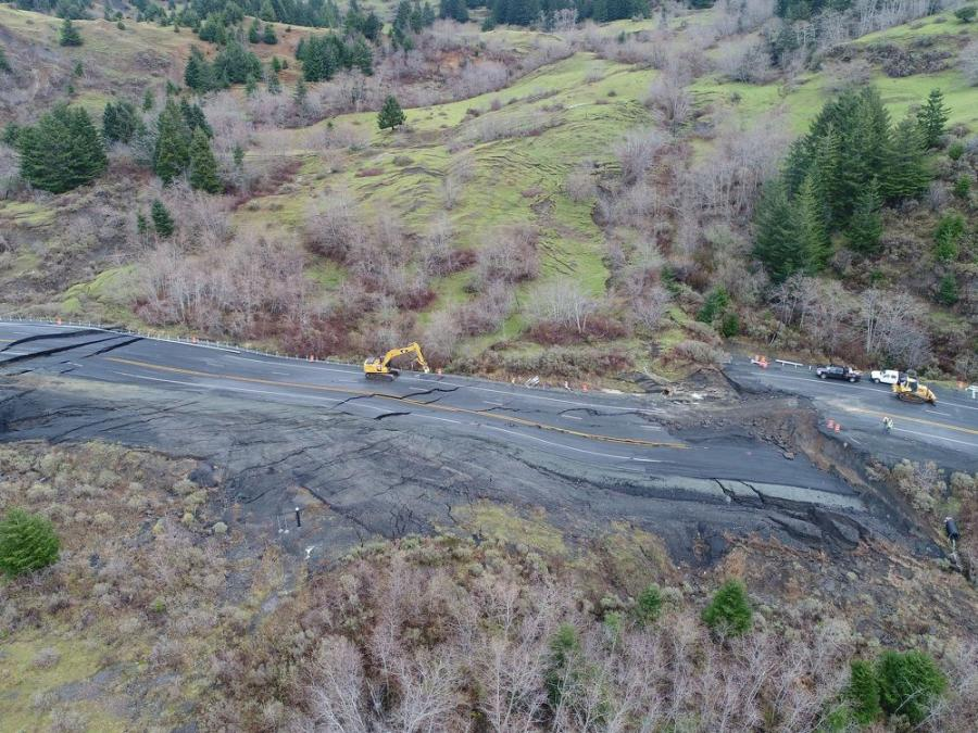 The slide in the Hooskanaden Creek area has cut off the town of Brookings from large truck deliveries and has forced travelers to use a winding, narrow mountain road that is in places one lane and gravel.