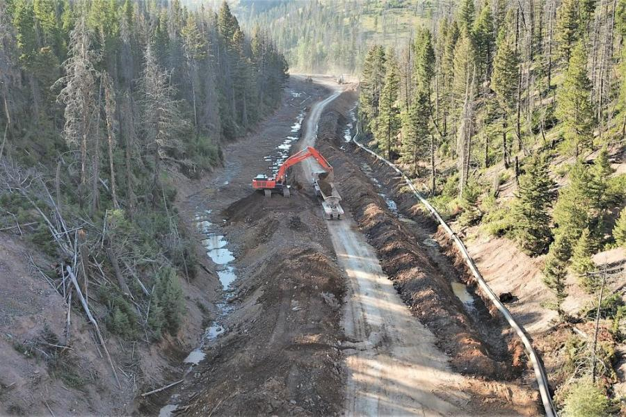 An MRC excavator loads a haul-truck. The creek is contained in the 19-in. pipeline to the right and the mounded material on which the excavator sits, as well as the roadway itself.