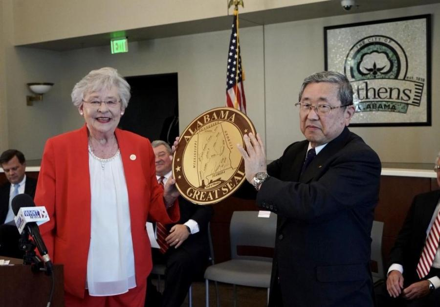 Alabama Gov. Kay Ivey and Shuhei Toyoda of Toyota Boshoku hold up the Alabama state seal as they announce plans for a $50 million manufacturing plant in Athens.