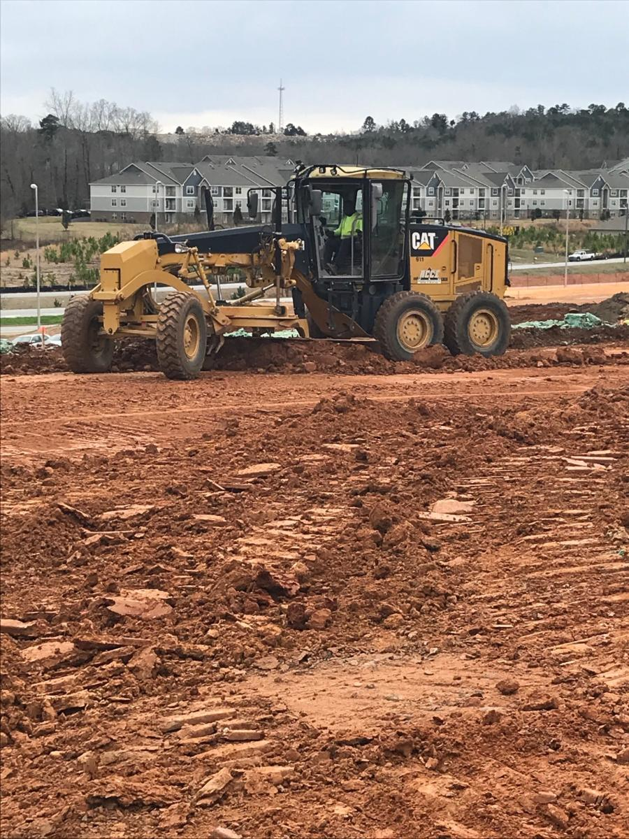 A motorgrader works the land in the initial stages of a $50 million development in Phenix City, Ala.