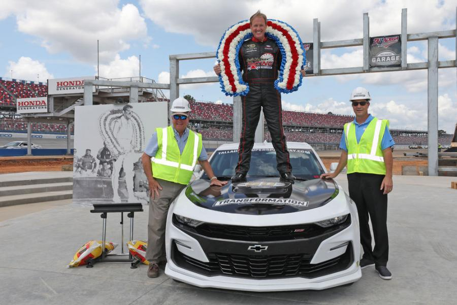 Hall of Fame driver Rusty Wallace (C), with help from Talladega Superspeedway Chairman Grant Lynch (L) and incoming track President Brian Crichton, introduce the track's newest tradition, the new red, white and blue wreath that will now be a part of future Gatorade Victory Lane ceremonies.