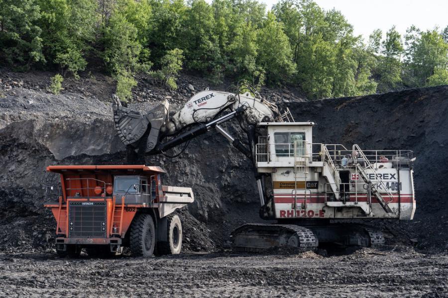 A Terex O&K RH120E loads overburden into a Hitachi EH1700-3 rigid frame truck.