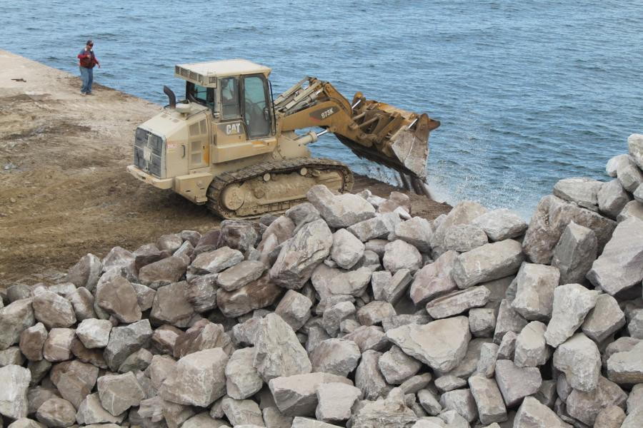 The boulders are pushed off the deck of the rock barge using a track loader. The placement of rock is between 38 and 48 ft. of water.