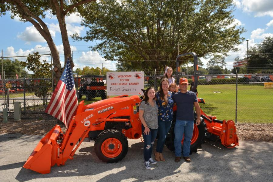 Marine Corps veteran Russell Guzzetta, owner of Country Song Farm in Lithia, Fla., and his family stands in front of the Kubota L Series compact tractor he was awarded through Kubota's Geared to Give program.