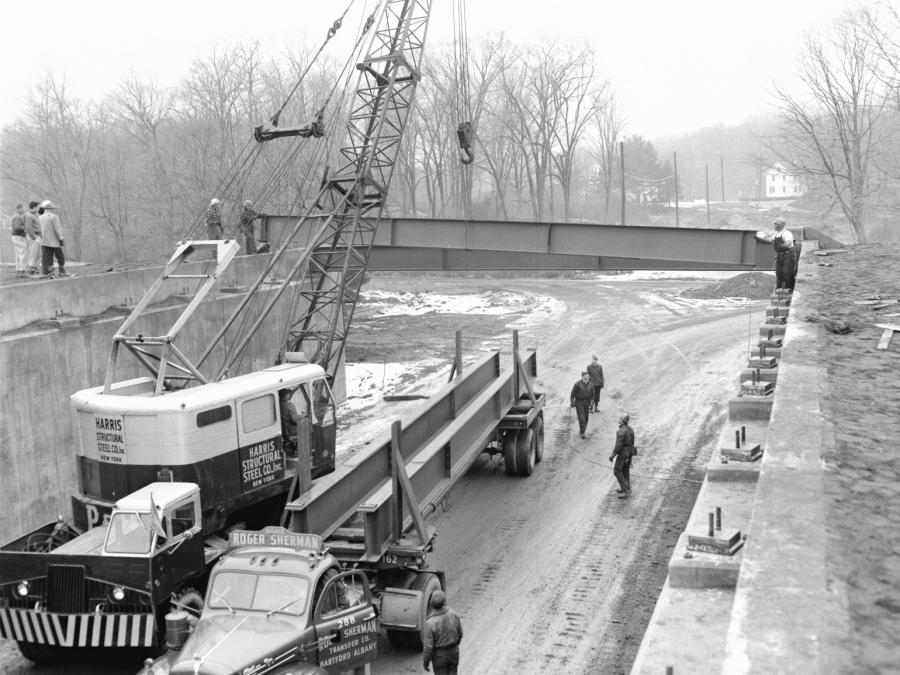 The P&H crane continues to hoist the steel beams into place. The beams were hauled to the project by Roger Sherman Transfer Company of Hartford, Conn. The truck tractor is a B-model Mack.